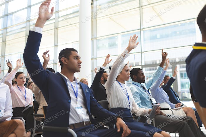 Side view of diverse business people raising hands in business seminar in office building