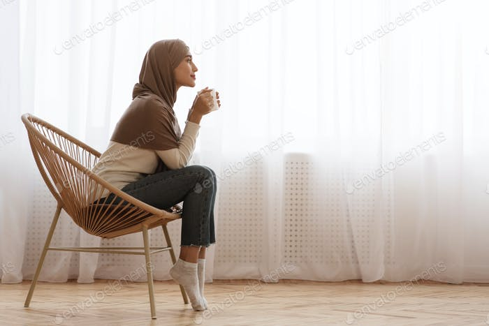 Arabic Woman In Headscarf Relaxing In Armchair With Coffee