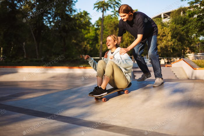 Pretty cheerful girl sitting on skateboard and riding with young