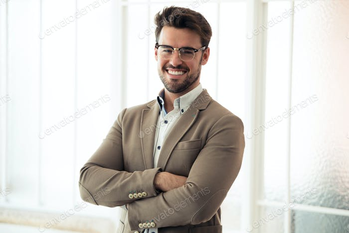 Handsome young business man looking at camera while standing in the office.