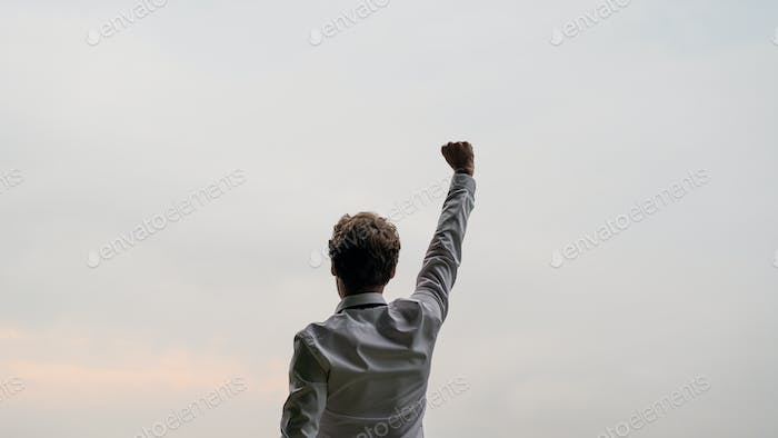 View from behind of a successful young businessman standing under the sky