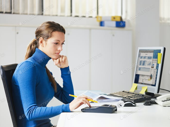 Female Young Secretary Using Calculator In Office
