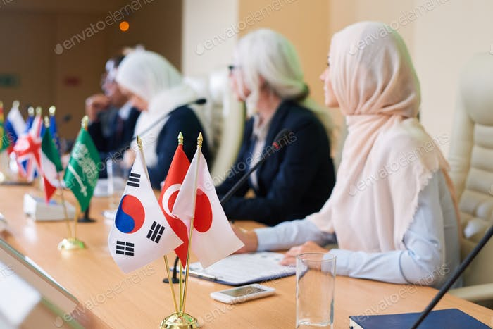 Bunch of flags of several foreign countries on table