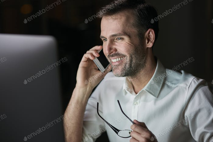 Close up of happy businessman talking by mobile phone