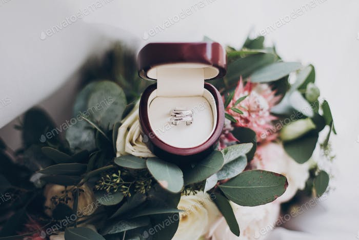 Silver wedding rings and stylish modern wedding bouquet of pink roses and green eucalyptus