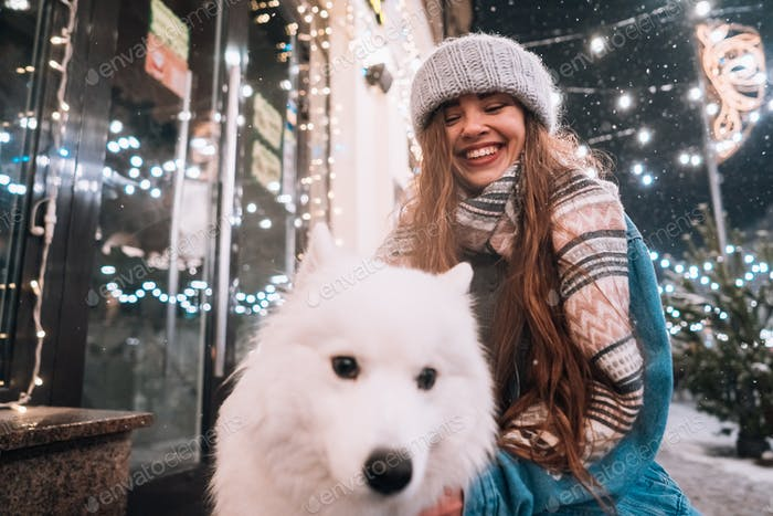 A young woman crouched beside a dog on a winter street