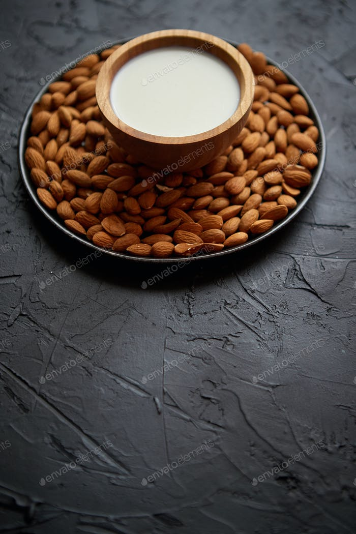 Composition of almonds seeds and milk, placed on black stone background