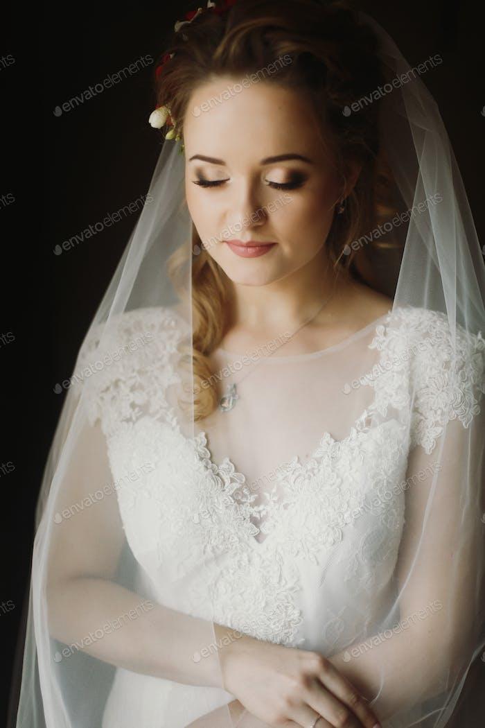 Porträt der schönen Braut, blonde Braut in eleganten weißen Hochzeitskleid mit Schleier posiert