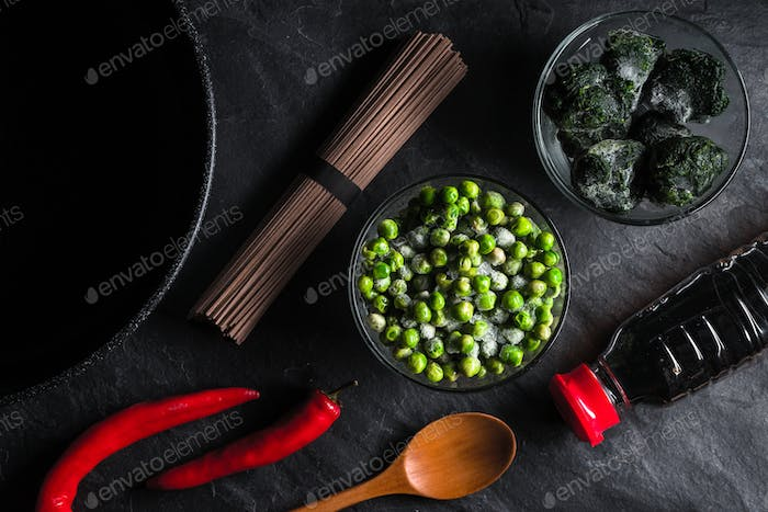 Buckwheat noodles, frozen spinach and peas, chili on a gray table