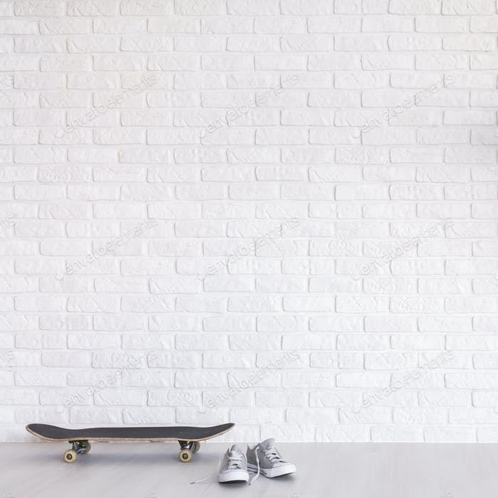 White room with a skateboard and sneakers