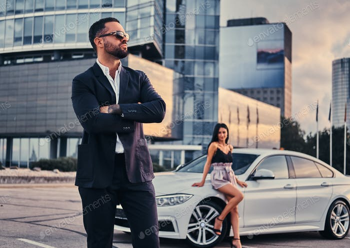 Well-dressed attractive couple leaning on a luxury car outdoors against the skyscraper.