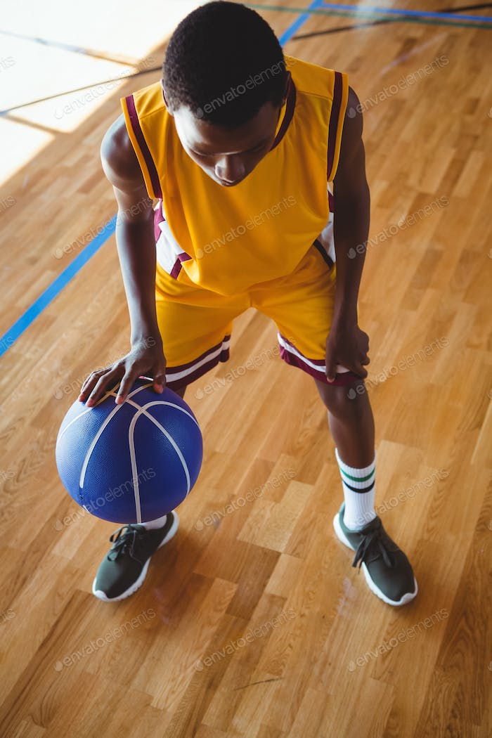 High angle view teenage boy practicing basketball