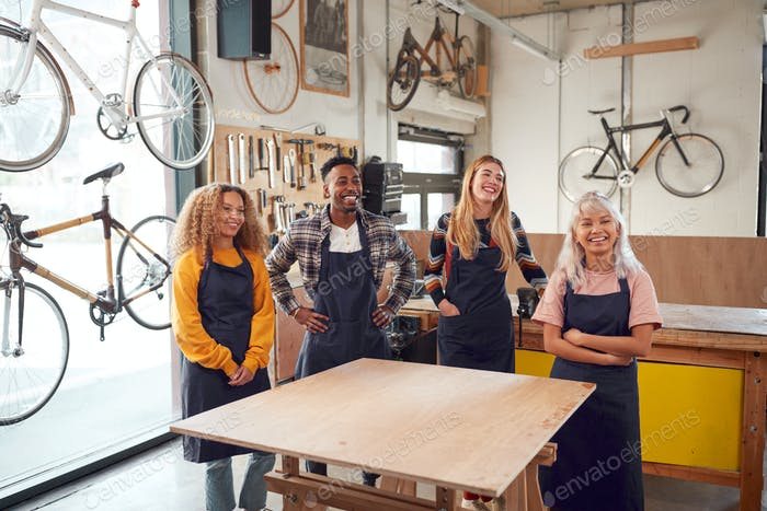 Multi-Cultural Team In Workshop Assembling Hand Built Sustainable Bamboo Bicycle Frame