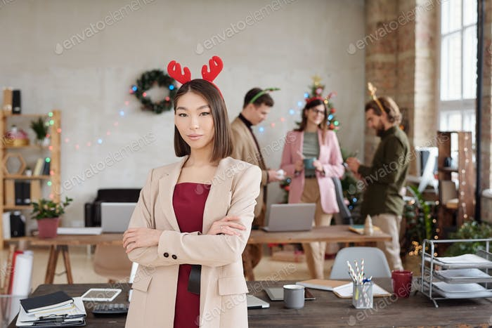 Young Asian businesswoman in smart casualwear and xmas headwear