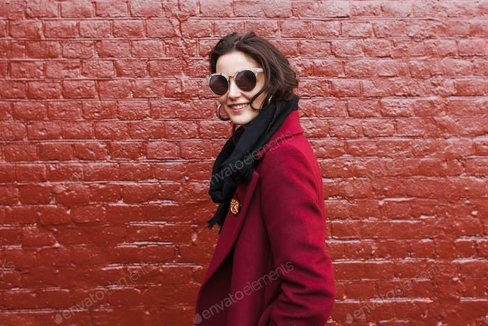 stylish smiling woman in sunglasses and red coat