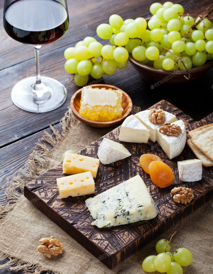 Red wine in glass with cheese, honey, nuts and grape.