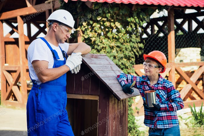 Father And Son Building Tree House Together Painting it With a Brush