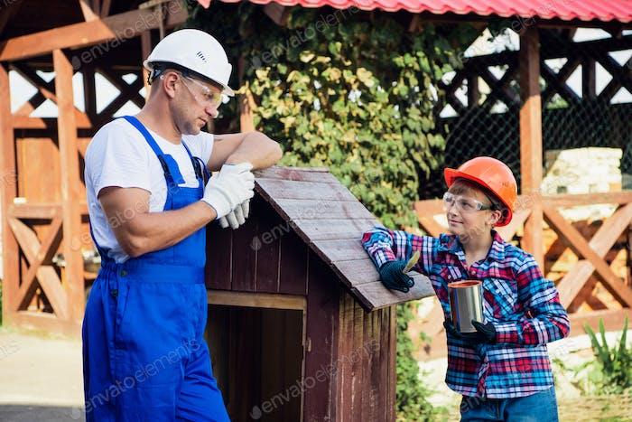 Vater und Sohn bauen Baum Haus zusammen Malerei es mit einem Pinsel