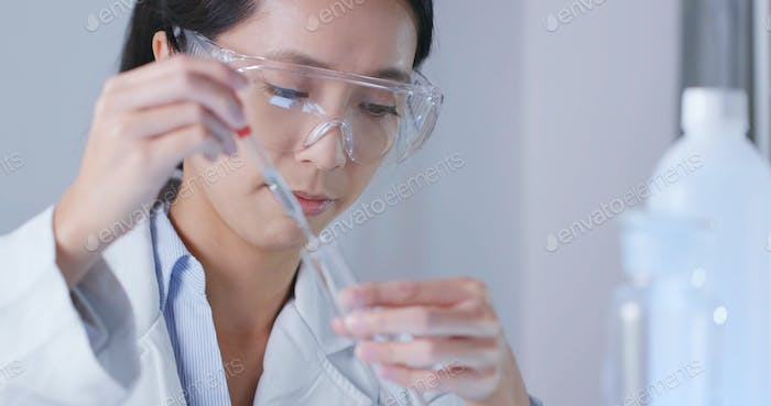 Scientist using looking at a test tube