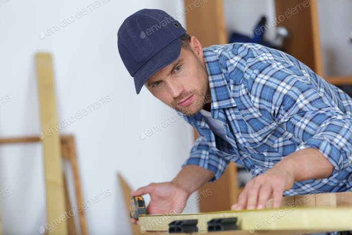 picture of young man working as carpenter and measuring board