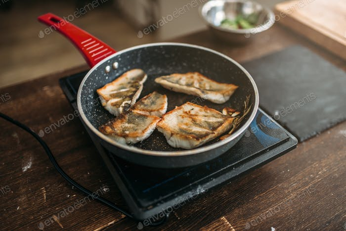 Frying pan with fried fish fillet, seafood cooking