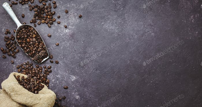 coffee beans in a sack on dark background, top view, copy space