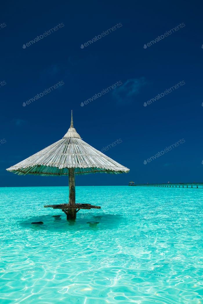 Bambus Sonnenschirm mit Barsitzen im Wasser einer Insel
