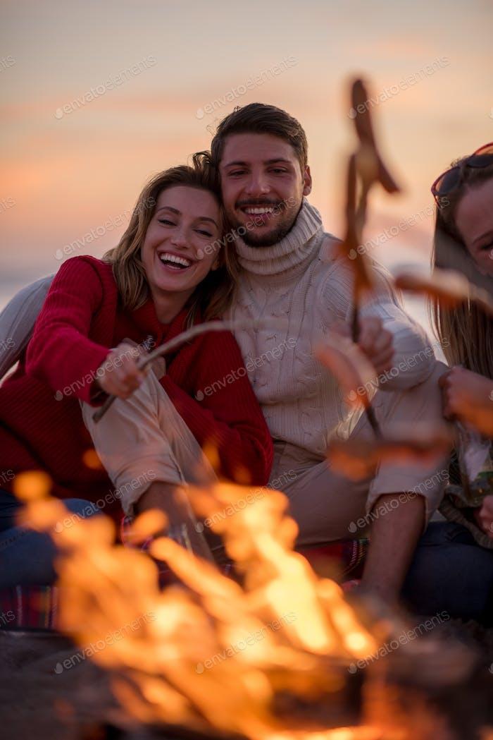 Gruppe von jungen Freunden sitzen durch die Feuer am Strand