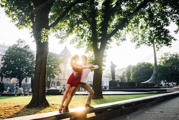 Couple in love embracing and dancing in evening sunlight in sunny street