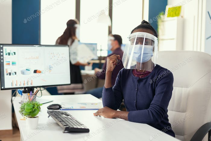 African entrepreneur in office wearing mask and face shield