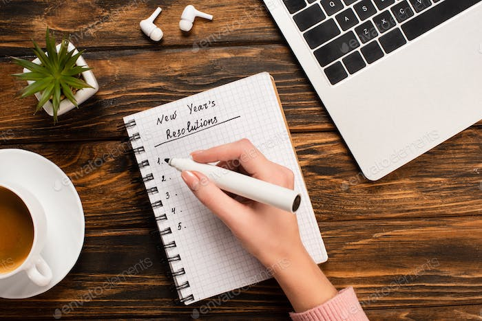 partial view of businesswoman writing new years resolutions near laptop, wireless earphones, potted