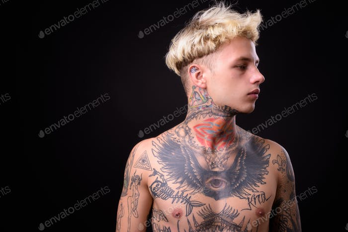 Young handsome rebellious man with tattoos shirtless