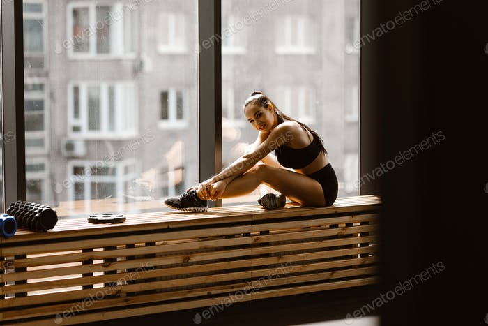 Athletic dark-haired girl dressed in black sports top and shorts is sitting on a wooden window sill