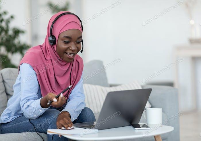 Online Tutoring. Friendly black muslim female tutor having video call with students