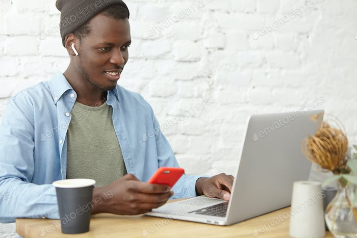 Trendy-looking smiling young dark-skinned man in hat using wireless earbuds while watching video or