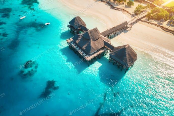 Luftansicht des schönen Hotels auf dem Wasser im Ozean bei Sonnenuntergang