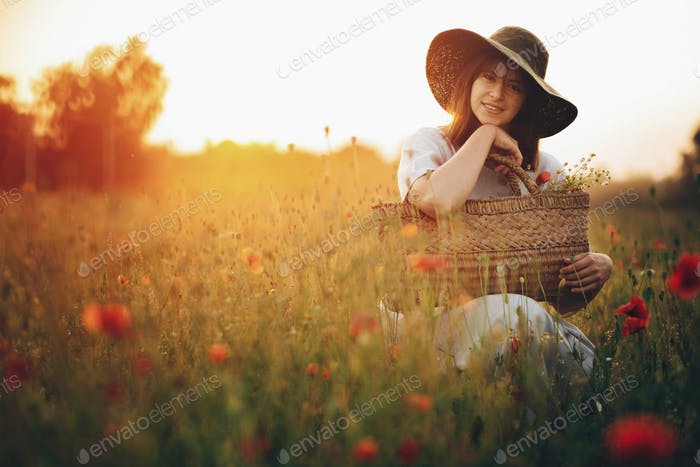 Stylish girl in linen dress smiling in poppy meadow in sunset light