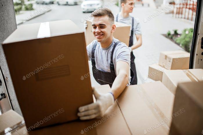 Ein junger, gutaussehender lächelnder Mover, der Uniform trägt, greift nach der Box, während der Van voll entladen wird