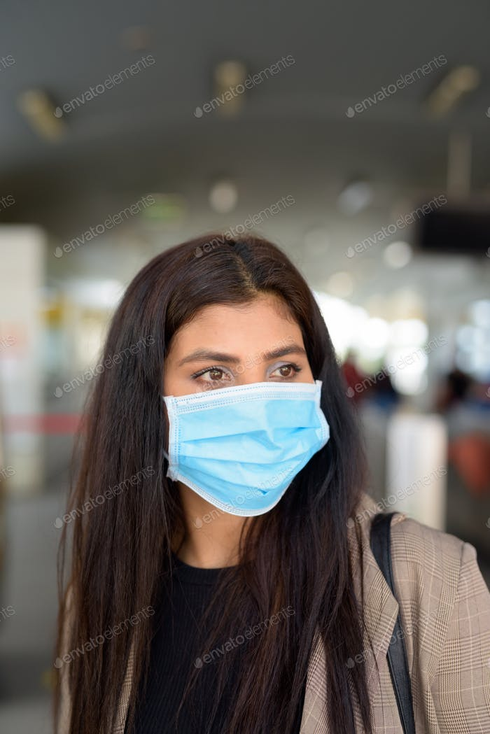 Face of young Indian businesswoman with mask thinking while buying ticket at skytrain station