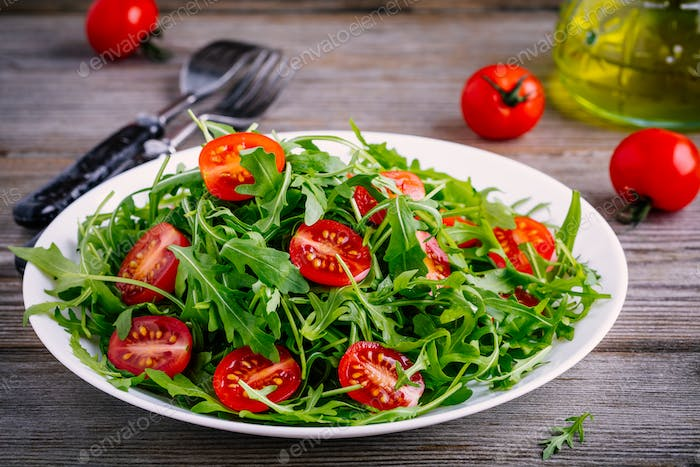 fresh green salad with arugula and red tomatoes on wooden background