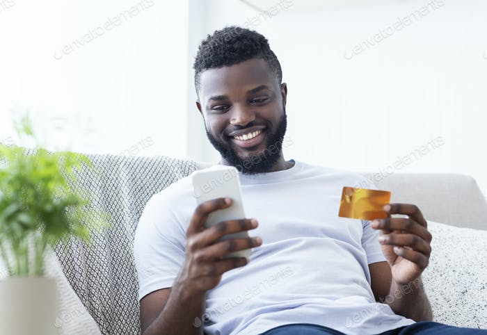 African american man holding credit card and cellphone