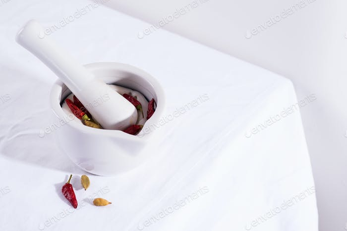White porcelain mortar and pestle with chili peppers and cardamom isolated on textile table, copy