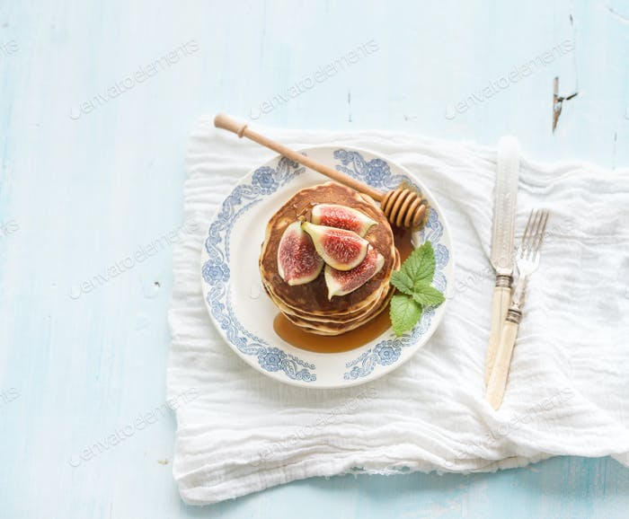 Pancake tower with fresh figs and honey on a rustic plate. Light blue  background