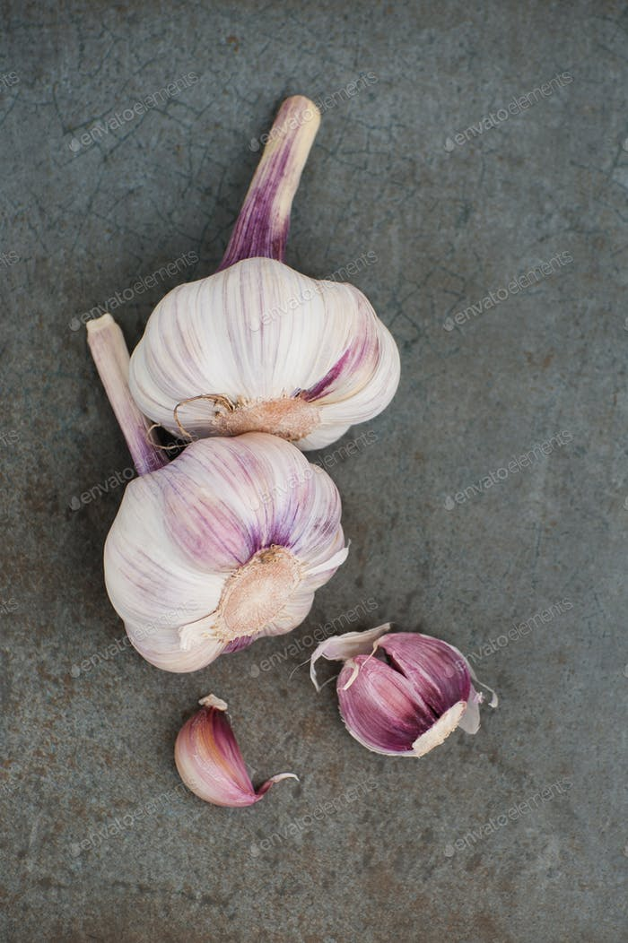 Young garlic on a blue-gray stone background.