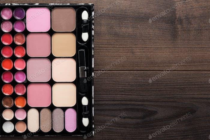Make-Up Palette On Brown Wooden Background