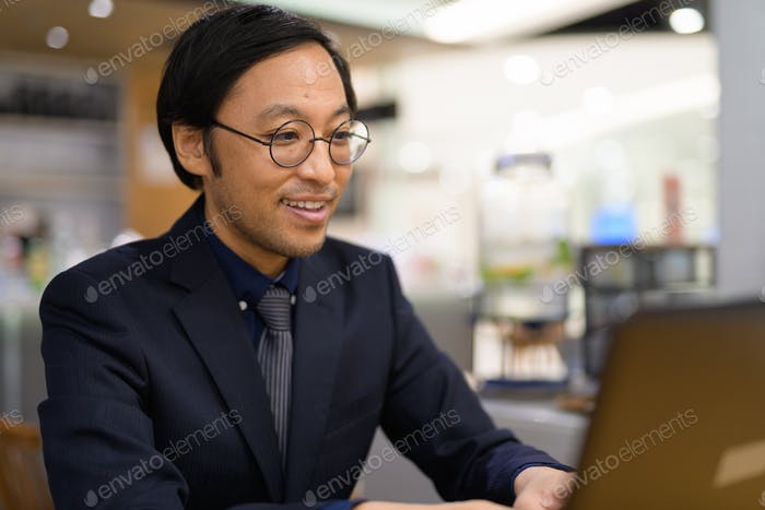 Happy Asian businessman using laptop at coffee shop