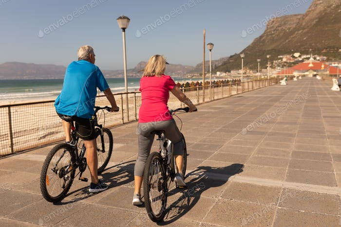 Rear view of senior couple riding a bicycle on a promenade at beach