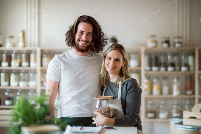A portrait of two shop assistants standing in zero waste shop, looking at camera.