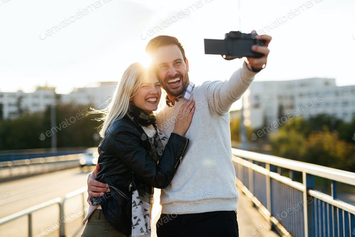 Beautiful young couple making selfie on bridge