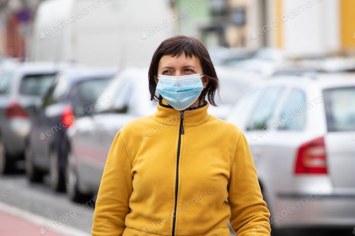 Porträt der brünetten Frau in einer medizinischen chirurgischen Maske in der Stadt.
